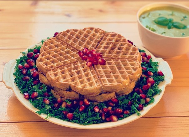 Savoury potato garlic waffles served with kale, pomegranate seeds, and cashew herb cream