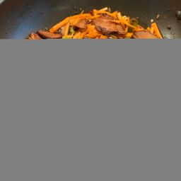 Frying shiitake, capsicum, and carrots in Szechuan sauce
